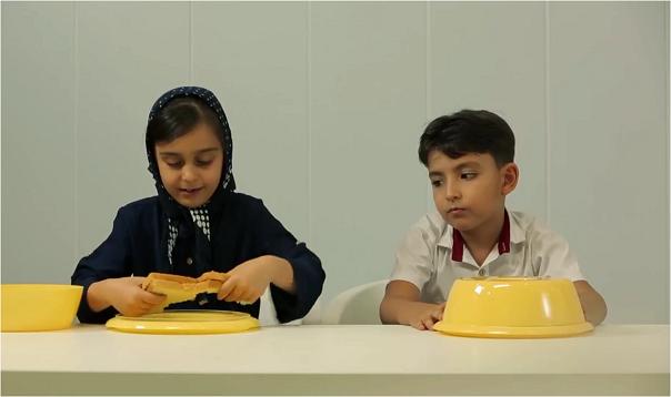 یک فریم از ویدیوی معروف اشتراک غذا توسط بچه ها که مصداقی از سنجش هوش تیمی در آن ها است.