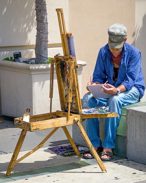 تصویری از یک نقاش که غرق در کار خود است با اشاره ای به تمرکز در ارائه ی بهترین عملکرد حرفه ای