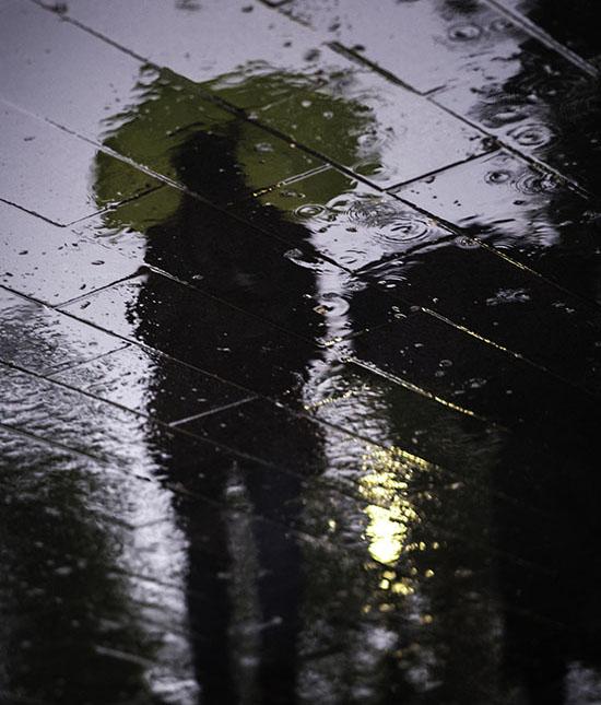 تصویری از رفلکس مردی با چتر در باران با مفهوم انتزاعی امنیت شغلی