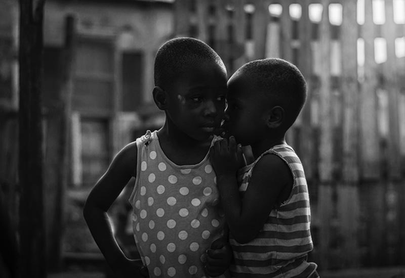 تصویر دو کودک که در گوشی صحبت می کنند، با الهام از مفهوم به اشتراک گذاری هدف ها.